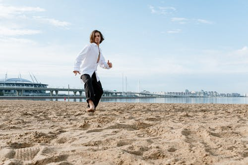 Woman in White Long Sleeve Shirt and Black Shorts Running on Beach