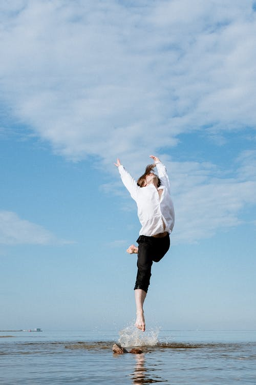 Man in White Dress Shirt and Black Shorts Standing Under Blue Sky