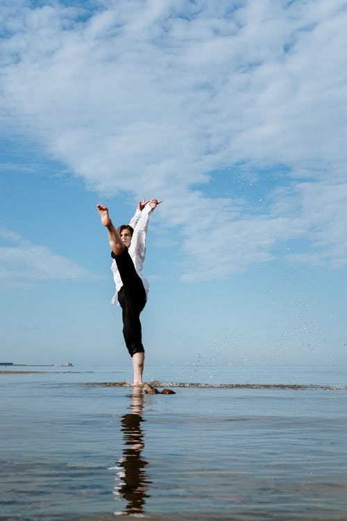 Woman in Black Dress Standing on Beach