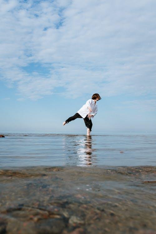 Girl in White Long Sleeve Shirt and Black Pants Running on Beach