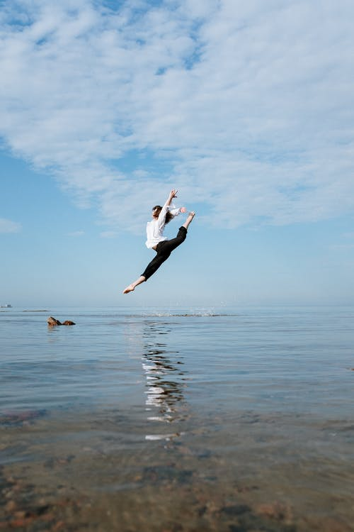 Woman in White Long Sleeve Shirt and Black Pants Jumping on Water