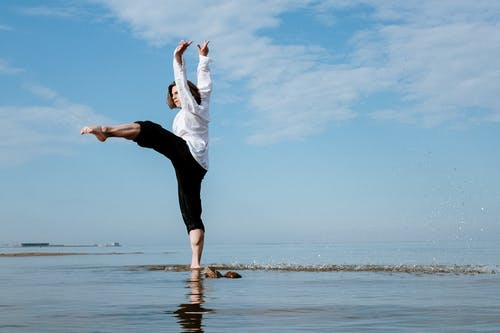 Woman in White Shirt and Black Leggings Jumping on Water