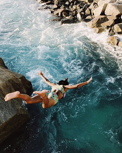 Woman in White Bikini Lying on Rock Formation Near Body of Water