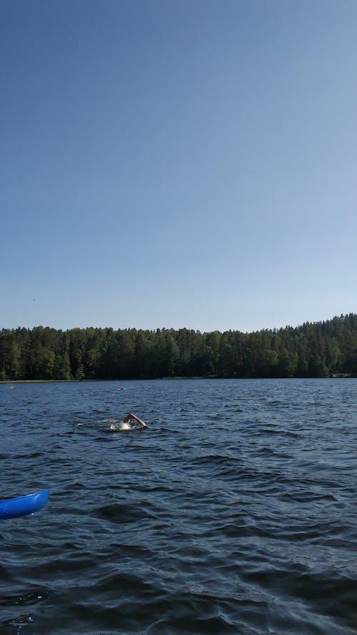 Person Riding on White Kayak on Blue Sea