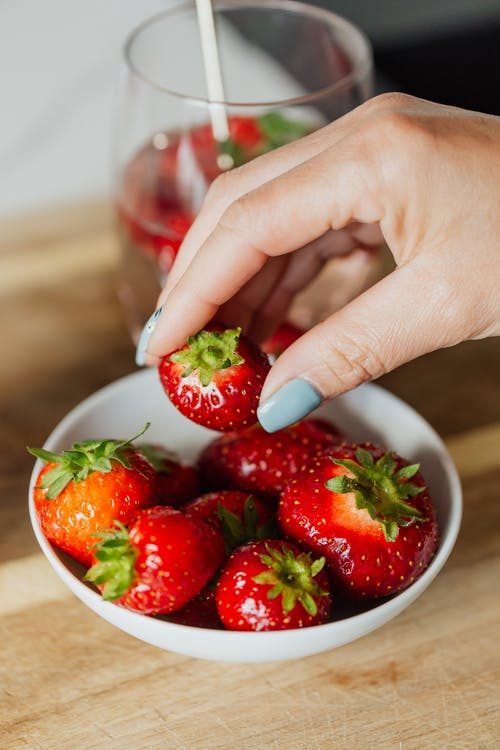 Person Holding White Ceramic Bowl With Strawberries