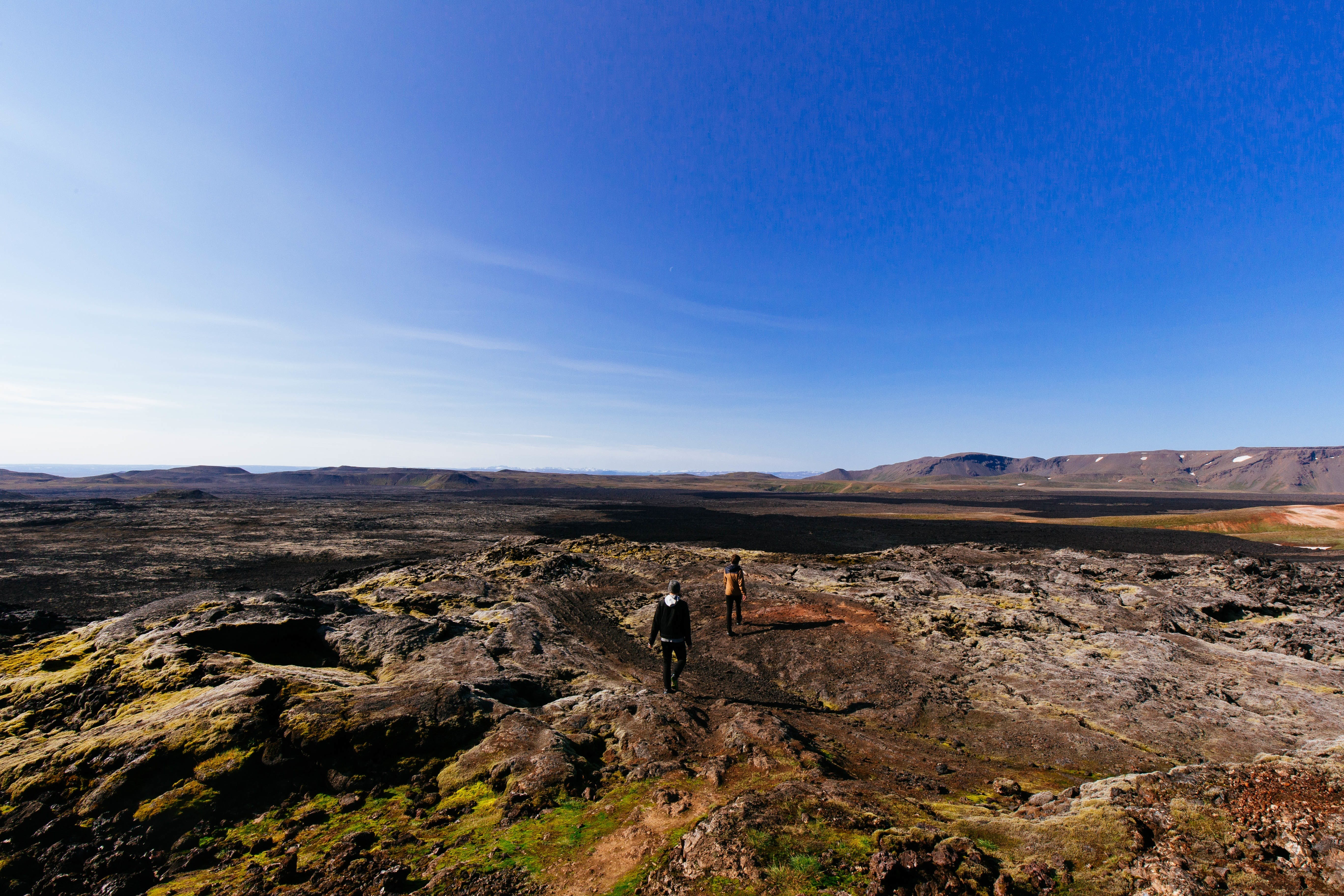 2 People Standing on Mountain Hill Under Clear Blue Sky
