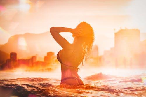 Young woman in bikini standing in water