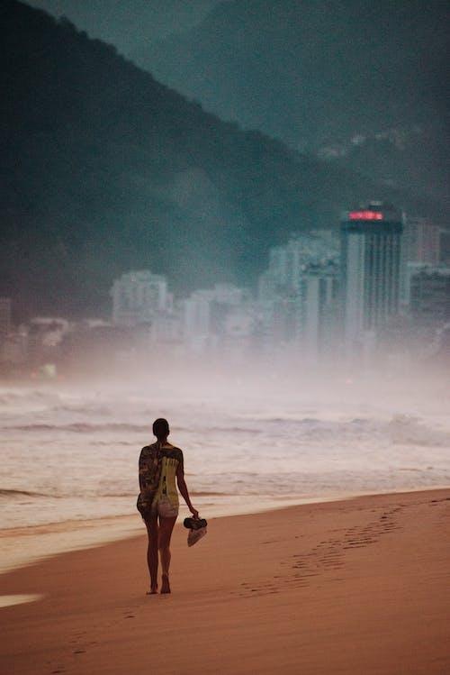 Unrecognizable ethnic woman walking on beach