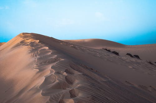 Picturesque view of sandy terrain in dry desert against blue sky in sunlight in summer day outside