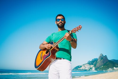 Low angle of content male in sunglasses playing acoustic guitar while standing on sandy beach near turquoise sea and looking at camera