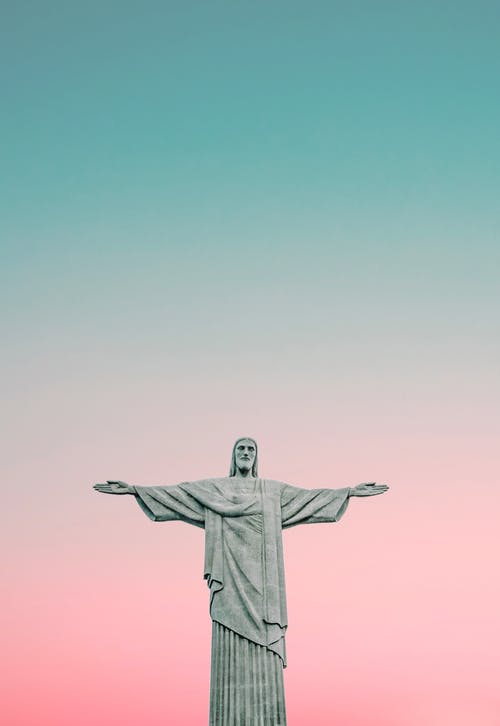 Low angle of sculpture of Christ redeemer with open arms placed against pink sky in famous Brazil at sunset time