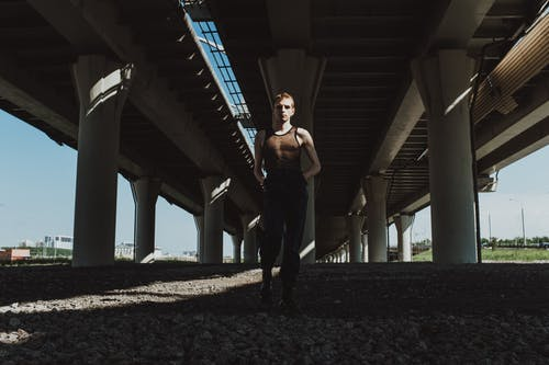 Man in Black Tank Top and Black Pants Standing Under Bridge