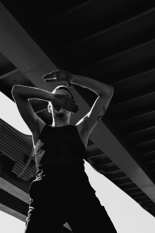Grayscale Photo of Woman in Black Tank Top Raising Her Hands