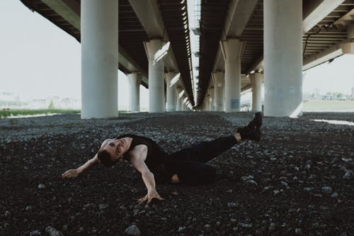 Man in Black Tank Top and Black Pants Lying on Ground Under White Concrete Bridge during