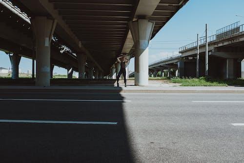 2 Person Walking on Gray Concrete Road Under Gray Concrete Bridge
