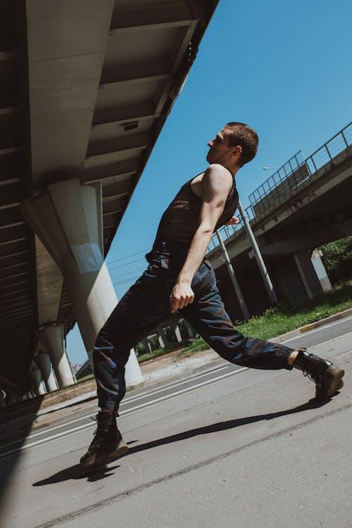 Man in Black Tank Top and Blue Denim Jeans Walking on Sidewalk