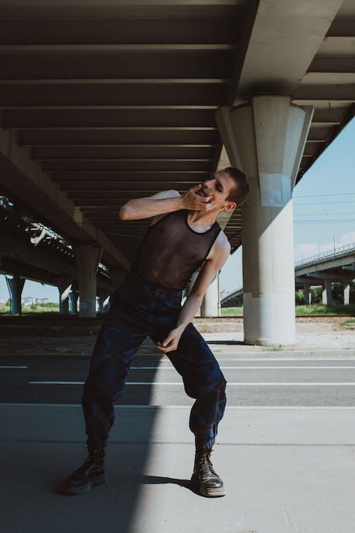 Man in Black Tank Top and Blue Denim Jeans Standing on Sidewalk