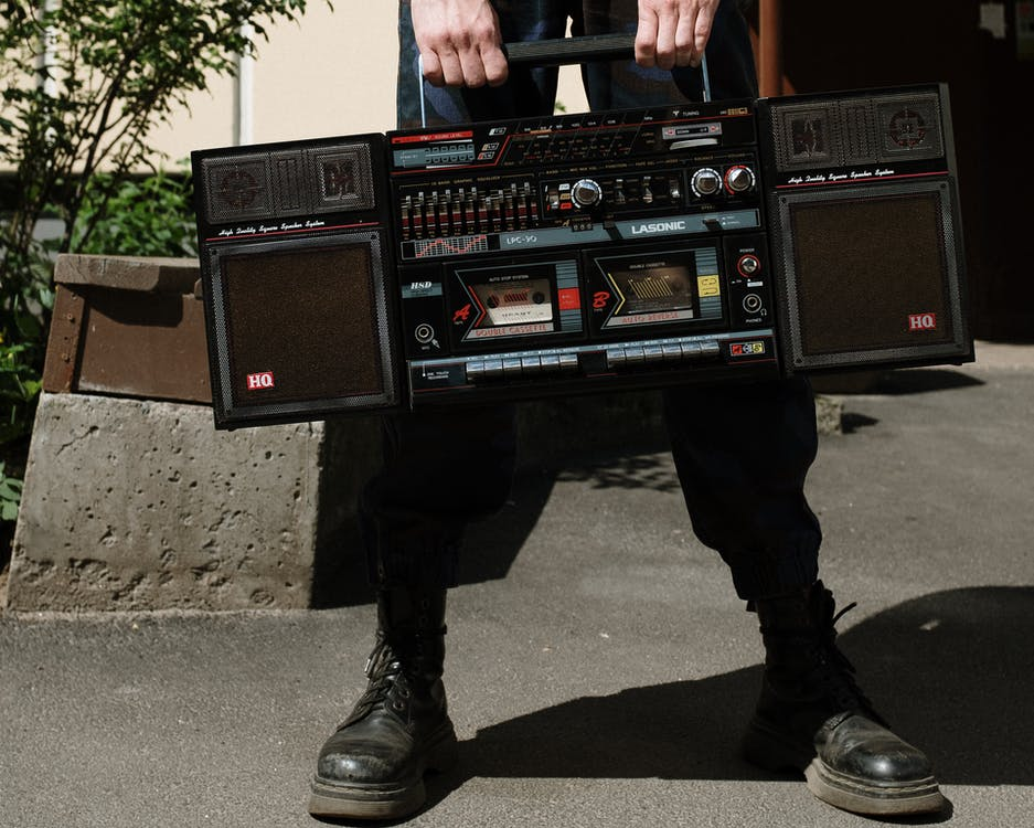 Man in Black Leather Boots Holding Black and Red Radio
