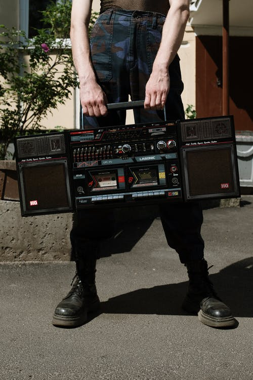 Man in Black Jacket and Black Pants Holding Black and Red Audio Mixer