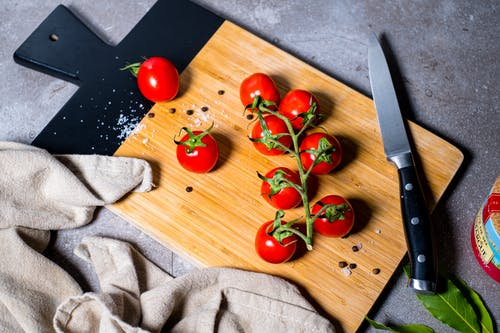 Red Tomato Beside Stainless Steel Bread Knife on Brown Wooden Chopping Board