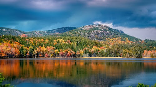 Autumn forest with colorful trees growing near mountain on coast of calm pond against cloudy sky