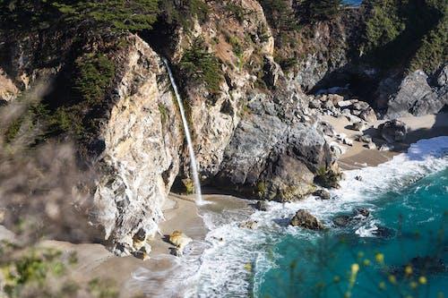 Amazing rocky seashore with waterfall streaming towards azure sea