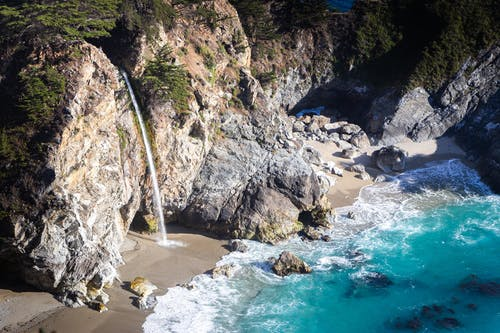 Amazing scenery of rocky cliff with rapid cascade flowing into turquoise transparent seawater on sunny day