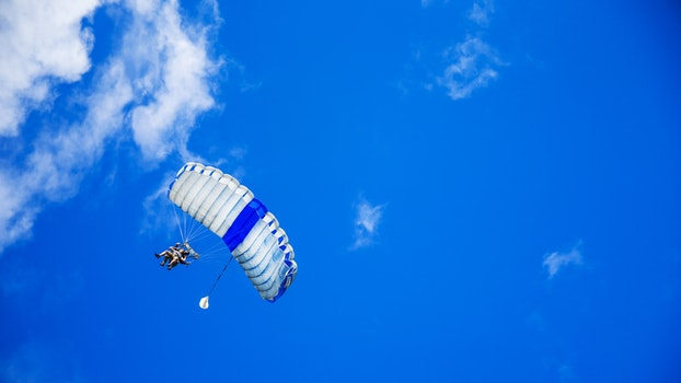 Person in Yellow Suit Flying With the Parachute Under Blue Calm Sky during Daytime