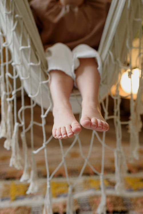 Crop unrecognizable barefoot kid sitting in hammock with fringe above floor at home in daylight
