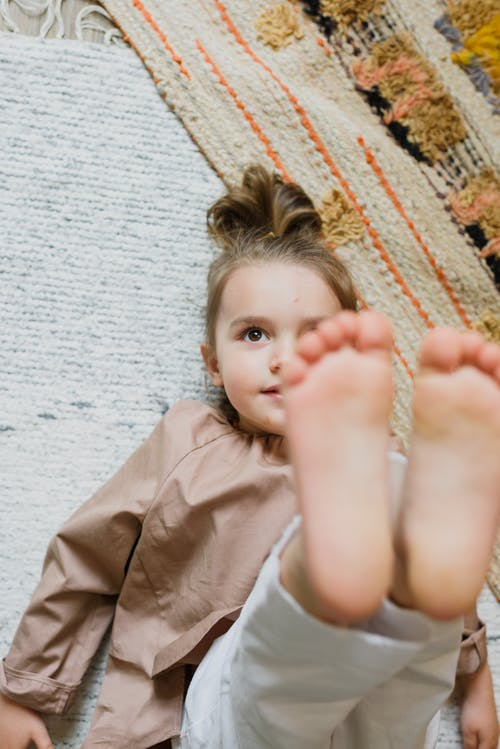 Smiling barefoot girl resting on carpet in house