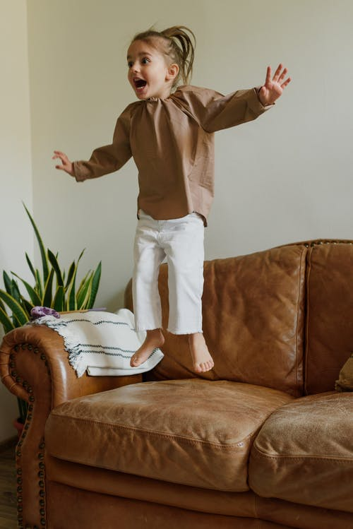 Excited girl jumping on couch in living room