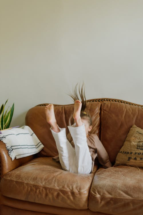 Anonymous child having fun on sofa in living room