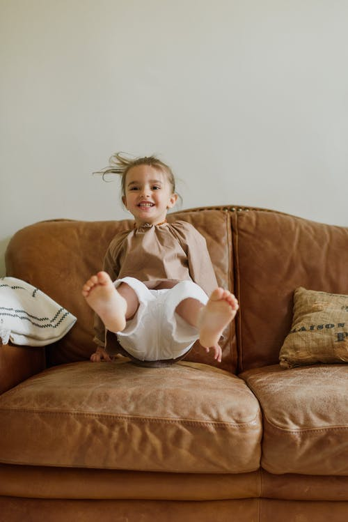 Cheerful girl jumping on sofa at home