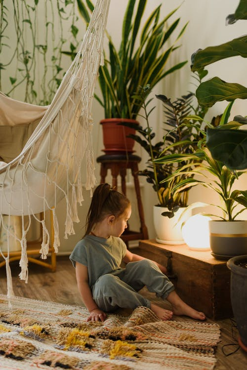 Little girl contemplating shiny lamp in living room