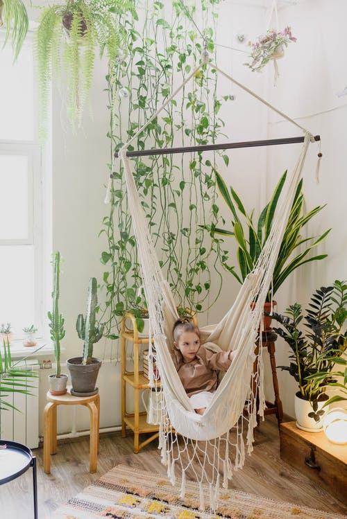 Cute girl resting in hammock in room with plants