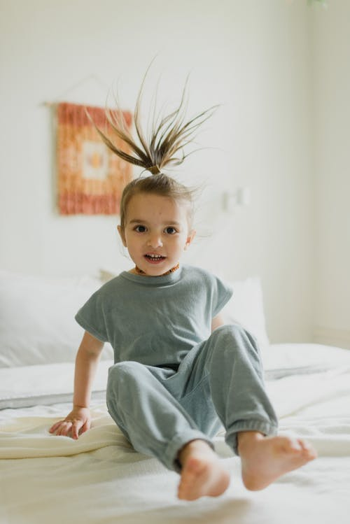Carefree girl with flying hair jumping on bed