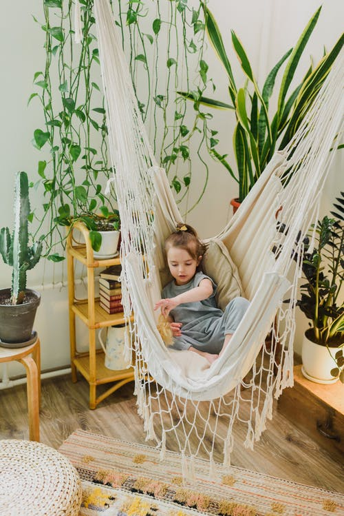 Little child playing in hammock at home