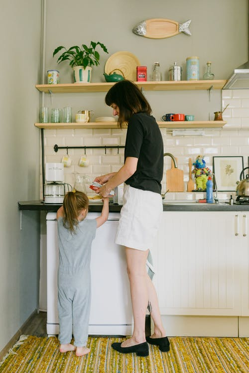 Young mother with little daughter preparing breakfast in kitchen