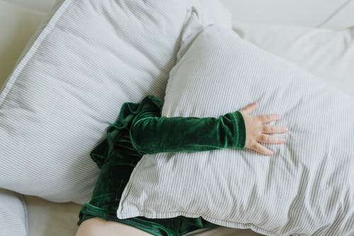 Top view of anonymous little kid in plush hoodie lying on soft bed and covering face with pillow
