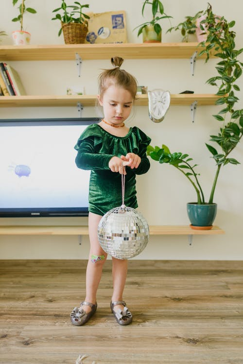 Adorable little child playing with mirrored ball at home