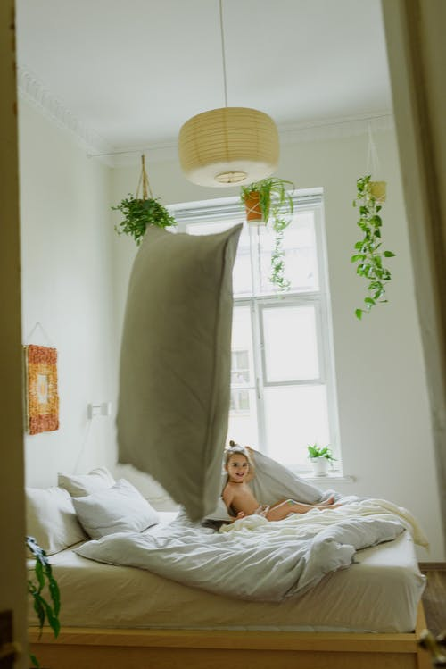 Side view of joyful little girl smiling and throwing pillows while playing on bed in cozy room