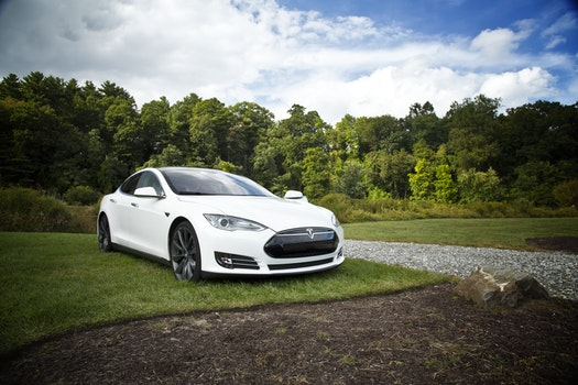 White Car on Green Grass Sorrounded by Trees Under White Clouds