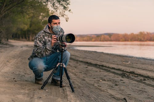 Man in Brown and Beige Camouflage Jacket and Blue Denim Jeans Sitting on Black Tripod
