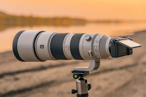 Black and Gray Camera Lens on Brown Sand