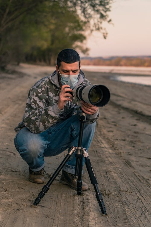 Man in Green and Brown Camouflage Jacket and Blue Denim Jeans Holding Black and Silver Dslr