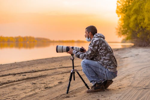 Man in Brown and Black Camouflage Jacket Sitting on Black Tripod