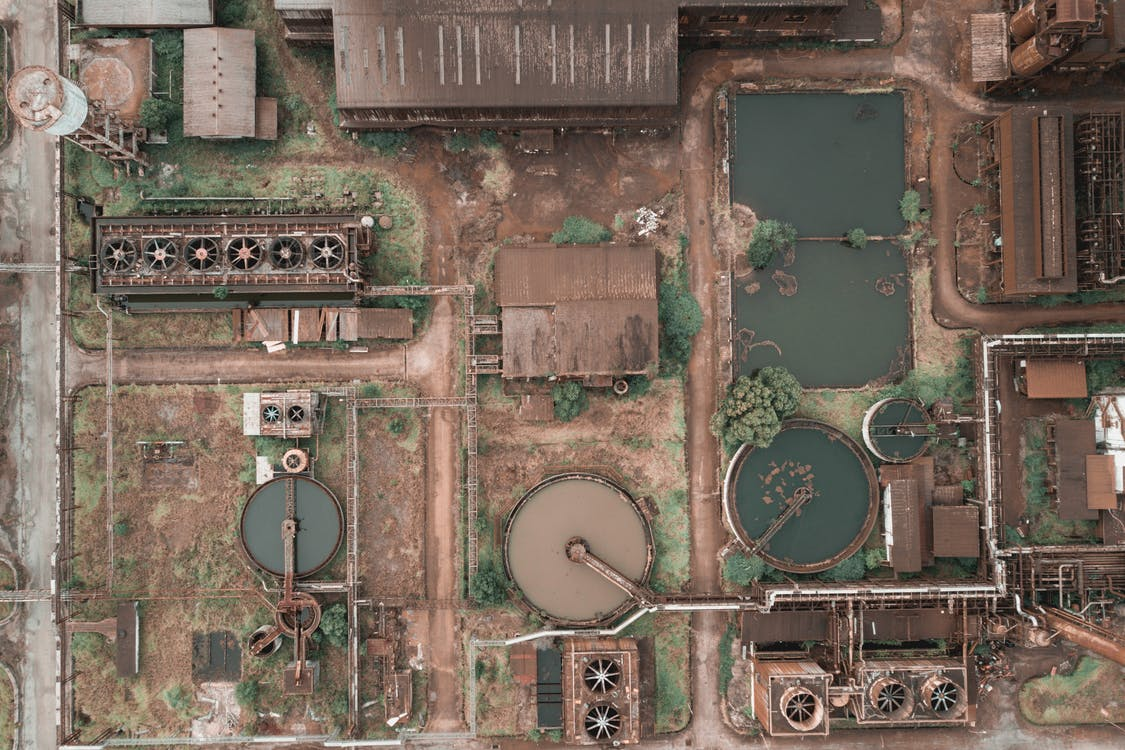 Drone view of abandoned chemical plant with rusty and unused production buildings and round tanks with dirty water