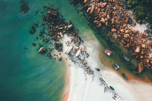Majestic drone view of shabby boats moored in  shallow water of sea with turquoise water near sandy shore with rocks