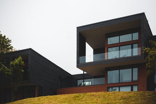 From below of contemporary geometric building with big windows and stylish design of balcony on green grass with trees