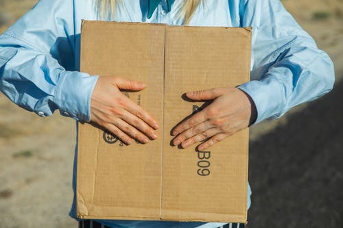 Person in Blue Long Sleeve Shirt Holding Brown Cardboard Box